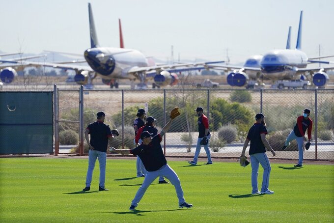 With mothballed and retired passenger planes in the background at Phoenix Goodyear Airport, pitchers for the Cleveland Indians warm up during a spring training baseball practice Monday, Feb. 22, 2021, in Goodyear, Ariz. (AP Photo/Ross D. Franklin)