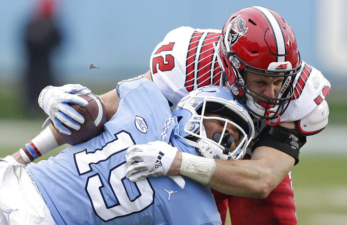 North Carolina State's Brock Miller (12) tackles North Carolina's Dazz Newsome (19) during the first half of an NCAA college football game in Chapel Hill, N.C., Saturday, Nov. 24, 2018. (AP Photo/Gerry Broome)