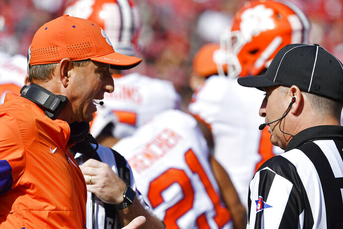Clemson head coach Dabo Swinney, left, argues with a game official during the first half of an NCAA college football game against Louisville in Louisville, Ky., Saturday, Oct. 19, 2019. (AP Photo/Timothy D. Easley)