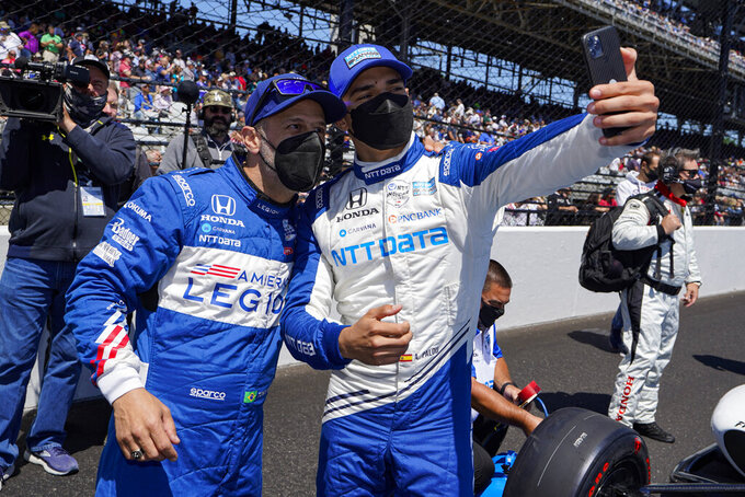 Tony Kanaan, left, of Brazil, and Alex Palou, of Spain, take a photo before the Indianapolis 500 auto race at Indianapolis Motor Speedway in Indianapolis, Sunday, May 30, 2021. (AP Photo/Michael Conroy)