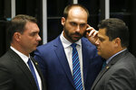 Senate President Davi Alcolumbre, right, talks with lawmaker Eduardo Bolsonaro, center, and Senator Flavio Bolsonaro, both sons of the nation's president, during the final voting session on pension reform at the Senate in Brasilia, Brazil, Tuesday, Oct. 22, 2019. The most meaningful impact is the establishment of a minimum age for retirement at 65 for men and 62 for women. (AP Photo/Eraldo Peres)