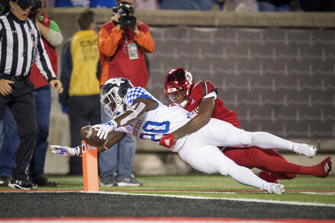 Kentucky running back Kavosiey Smoke (20) is tackled by Louisville safety Kaheem Roach (40) on a touchdown during the second half of the NCAA college football in Louisville, Ky., Saturday, Nov. 24, 2018. (AP Photo/Bryan Woolston)
