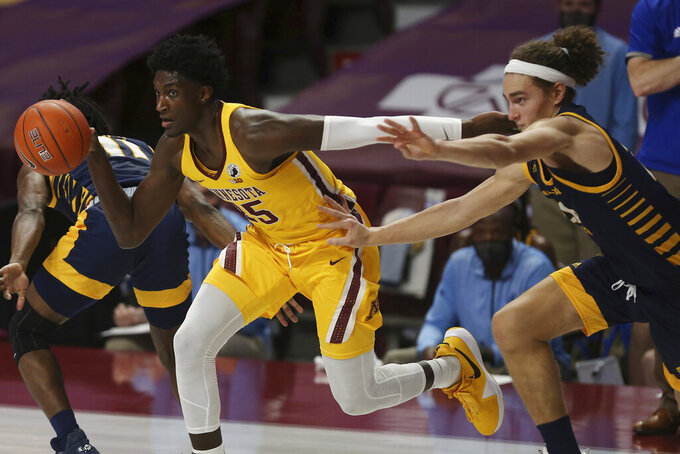Minnesota forward Isaiah Ihnen (35) controls the ball next to UMKC forward Josiah Allick, right, during the first half of an NCAA college basketball game Thursday, Dec. 10, 2020, in Minneapolis. (AP Photo/Stacy Bengs)