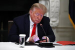 President Donald Trump looks at his phone during a roundtable with governors on the reopening of America's small businesses, in the State Dining Room of the White House, Thursday, June 18, 2020, in Washington. (AP Photo/Alex Brandon)