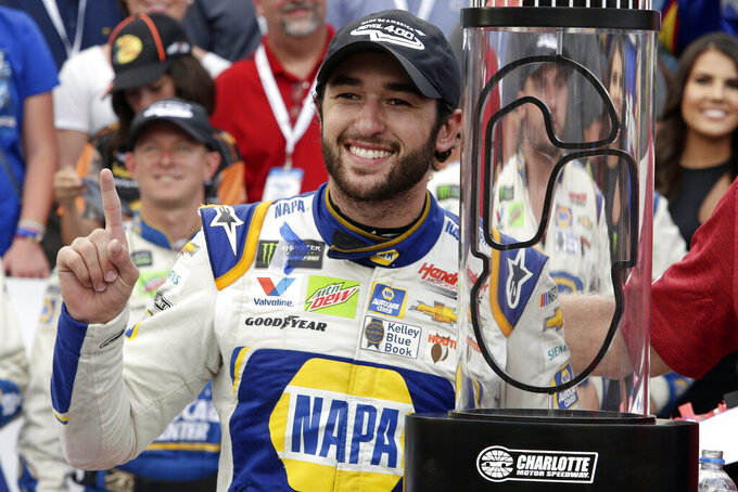 Chase Elliott poses with the trophy after winning the NASCAR Cup Series auto race at Charlotte Motor Speedway in Concord, N.C., Sunday, Sept. 29, 2019. (AP Photo/Wesley Broome)