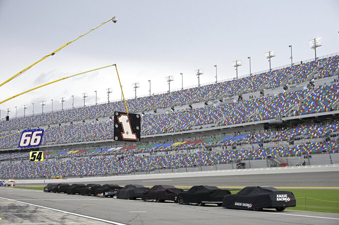 Cars sit covered on pit road during a severe weather delay in a NASCAR Xfinity Series auto race at Daytona International Speedway, Friday, Aug. 27, 2021, in Daytona Beach, Fla. (AP Photo/Phelan M. Ebenhack)