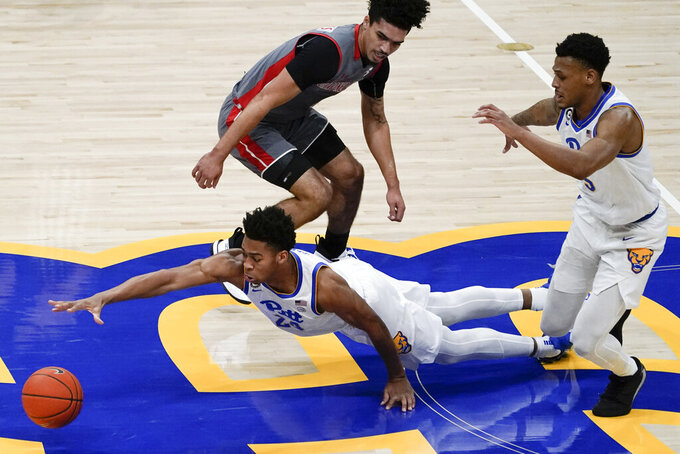 Pittsburgh's William Jeffress (24) dives for a loose ball in front of Gardner Webb's D'Maurian Williams, top, as Au'diese Toney chases, right, during the first half of an NCAA college basketball game, Saturday, Dec. 12, 2020, in Pittsburgh. (AP Photo/Keith Srakocic)