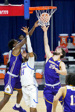 Western Illinois' Tamell Pearson, left, and Will Carius (25) battle DePaul's Nick Ongenda for a rebound during the second half of an NCAA college basketball game Wednesday, Dec. 23, 2020, in Chicago. (AP Photo/Charles Rex Arbogast)