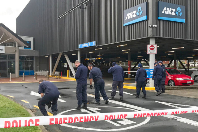 Police search outside the Chartwell Shopping Centre in Hamilton, New Zealand, Thursday, Aug. 6, 2020. Would-be thieves appear to have denoted two homemade bombs at an ATM machine outside a shopping mall early Thursday and left other unexploded bombs behind, according to police. (Belinda Feek/NZ Herald via AP)