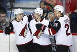 Arizona Coyotes' Conor Garland, centre, celebrates his goal with teammates Clayton Keller, left, and Nick Cousins during second period NHL hockey action against the Calgary Flames in Calgary, Alberta, Monday, Feb. 18, 2019. (Jeff McIntosh/The Canadian Press via AP)