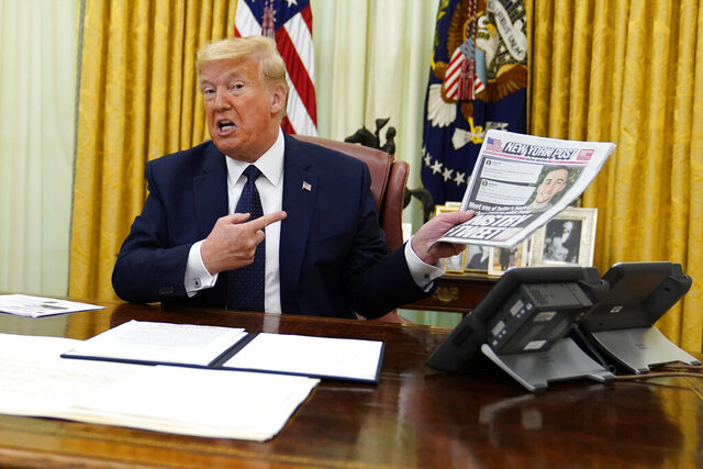 President Donald Trump holds up a copy of the New York Post as speaks before signing an executive order aimed at curbing protections for social media giants, in the Oval Office of the White House, Thursday, May 28, 2020, in Washington. (AP Photo/Evan Vucci)