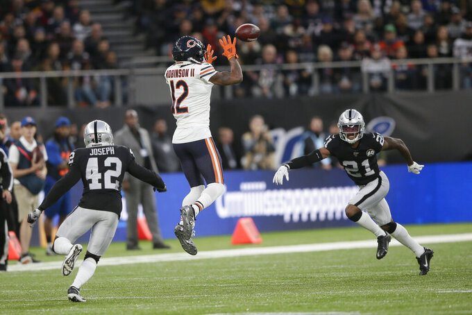 Chicago Bears wide receiver Allen Robinson (12) makes a catch against Oakland Raiders free safety Karl Joseph (42) and cornerback Gareon Conley (21) during the first half of an NFL football game at Tottenham Hotspur Stadium, Sunday, Oct. 6, 2019, in London. (AP Photo/Tim Ireland)