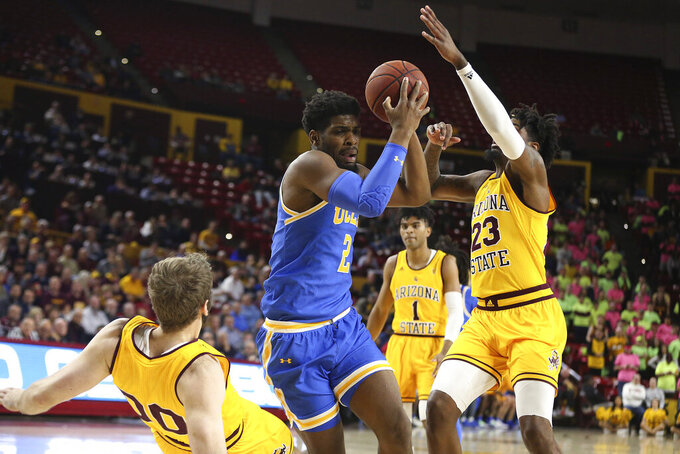 UCLA's Cody Riley (2) knocks down Arizona State's Mickey Mitchell (00) as Arizona State's Romello White (23) goes for the ball during the first half of an NCAA college basketball game Thursday, Feb. 6, 2020, in Tempe, Ariz. (AP Photo/Darryl Webb)