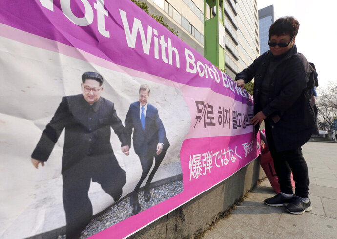 A woman displays a banner showing a photo of North Korean leader Kim Jong Un and South Korean President Moon Jae-in, right, to wish for peace on the Korean Peninsula, in Seoul, South Korea, Tuesday, March 19, 2019. International journalists' organizations have expressed concern over South Korea's press freedoms after the country's ruling party singled out a Bloomberg reporter over what it claimed was a