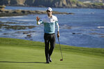 Nick Taylor, of Canada, waves after making a birdie putt on the 18th green of the Pebble Beach Golf Links during the second round of the AT&T Pebble Beach National Pro-Am golf tournament Friday, Feb. 7, 2020, in Pebble Beach, Calif. (AP Photo/Eric Risberg)