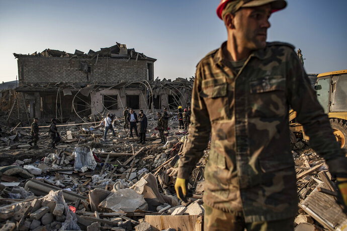 Azerbaijani soldiers and firefighters look for survivors from destroyed houses in a residential area in Ganja, Azerbaijan's second largest city, near the border with Armenia, after rocket fire overnight by Armenian forces for second time in a week, early Saturday, Oct. 17, 2020. Azerbaijan has accused Armenia of striking its second-largest city with a ballistic missile that killed at least 13 civilians and wounded 50 others in a new escalation of their conflict over Nagorno-Karabakh. (Can Erok/DHA via AP)