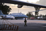 In this photo taken on Friday, March 4, 2016, A Russian military police officer stands guard at the Russian air base in Hemeimeem, Syria, with an Il-20 electronic intelligence plane of the Russian air force is in the background. An Il-20 aircraft was shot down Tuesday, Sept. 18, 2018 by a Syrian missile over the Mediterranean Sea, killing all 15 people on board, as the Syrian military fired on Israeli fighter jets attacking targets in northwestern Syria. (AP Photo)