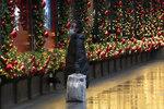 A shopper looks at Macy's window displays, Monday, Nov. 30, 2020, in New York. (AP Photo/Mark Lennihan)