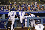 Los Angeles Dodgers' Mookie Betts, center, celebrates his home run with manager Dave Roberts during the fifth inning of a baseball game against the San Diego Padres, Thursday, Aug. 13, 2020, in Los Angeles. (AP Photo/Jae C. Hong)