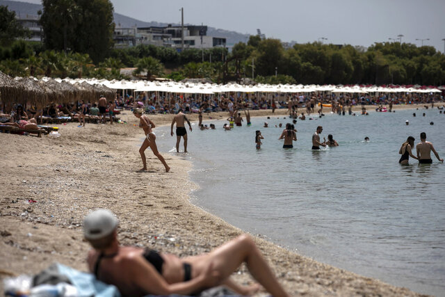FILE - Swimmers enjoy the sea and the sun at Alimos beach, near Athens, on Saturday, May 16, 2020. The quality of bathing waters in Europe remains high according to a study released by the EU environment agency on Monday, June 8, 2020, concluding that minimum water quality standards were met at 95 percent of the sites monitored across the continent last year. (AP Photo/Yorgos Karahalis, File)