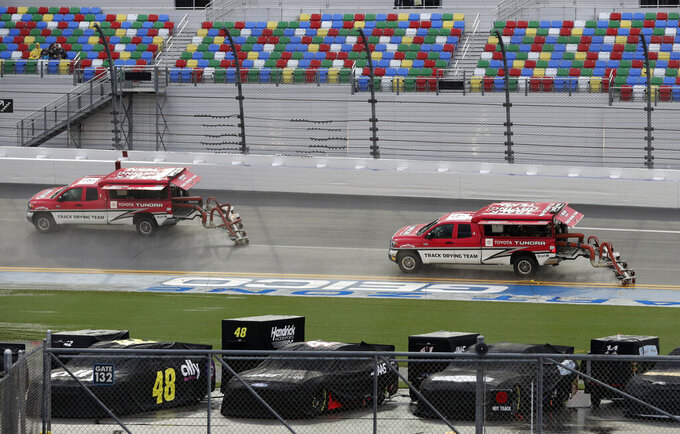 Special dryer-equipped trucks try to remove water from the track surface during a rain shower shortly before the scheduled start of a NASCAR Cup Series auto race at Daytona International Speedway, Saturday, July 6, 2019, in Daytona Beach, Fla. (AP Photo/John Raoux)