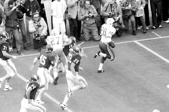FILE - In this Nov. 25, 1971, fie photo, Nebraska's Joe Blahak (27) delivers the final block to spring Johnny Rodgers (20) for a touchdown on a punt return in the first quarter of an NCAA college football game in Norman, Okla. Reports that Nebraska wants to back out of playing at Oklahoma this season didn't sit well with one of the stars of the 1971 Game of the Century. The game scheduled Sept. 18 in Norman, Oklahoma, would mark the 50th anniversary of Nebraska's 35-31 win over the Sooners in a clash of the Nos. 1 and 2 teams in the nation. (Bob Gorham/Lincoln Journal Star via AP, File)