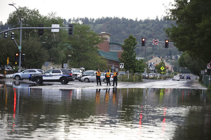 FILE — In this Tuesday, Aug. 17, 2021, file photo Flagstaff police officers stand at the edge of street flooding in Flagstaff, Ariz. After touring a small community where flooding inundated homes and led two deaths, Gov. Doug Ducey, on Friday, Aug. 20, praised the community of Gila Bend and other areas of the state that have endured flooding from this year's summer monsoon rains. (Jake Bacon/Arizona Daily Sun via AP, File)/Arizona Daily Sun via AP)