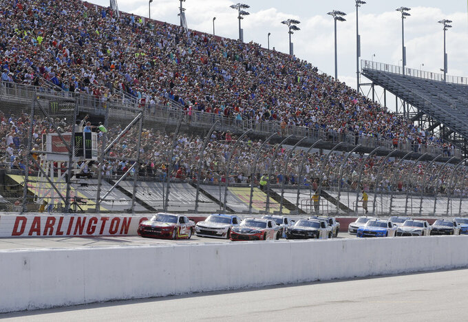 FILE - In this Aug. 31, 2019, file photo, Ryan Blaney leads the field to the start the NASCAR Xfinity Series auto race at Darlington Raceway in Darlington, S.C. NASCAR will resume its season without fans starting May 17 at Darlington Raceway in South Carolina. As NASCAR speeds back to the race track during the coronavirus pandemic the series has a heavy responsibility to set a safety standard that doesn't slow the return of other sports. (AP Photo/Terry Renna, File)