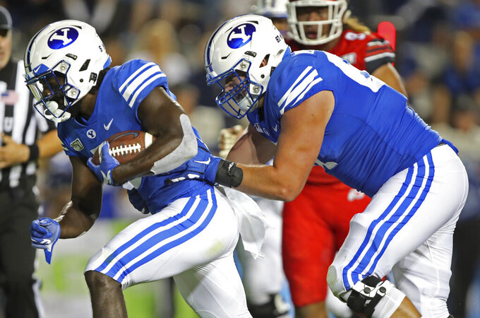 FILE - BYU offensive lineman Brady Christensen, right, pushes running back Ty'Son Williams, left, for a touchdown in the second half during an NCAA college football game in Provo, Utah, in this Thursday, Aug. 29, 2019, file phto A deal BYU has made available to its football players could test how much allowing athletes to be compensated by outside companies for name, image and likeness can be used as a competitive advantage. On Thursday, BYU announced Built Brands —- a Utah-based company that makes protein-heavy snacks —- will give the opportunity for all 123 members of its football team to be paid to promote its products. . (AP Photo/George Frey, File)