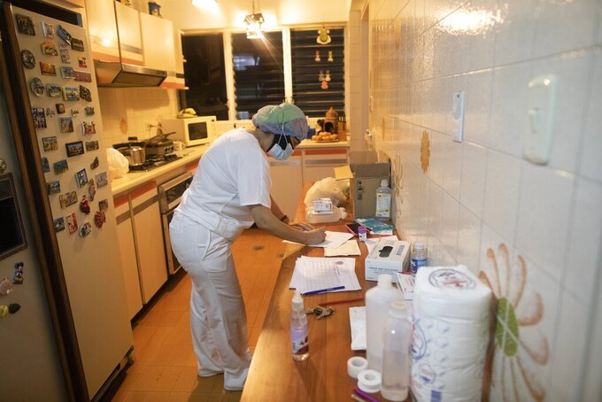 Nurse Marlene Cabezas takes notes on a table full of medical supplies and medicines, during a visit by a doctor to Carmen Lares and husband Oscar Lares' home in Caracas, Venezuela, Thursday, March 18, 2021. The Lares family is being treated at home for the last 4 days. (AP Photo/Ariana Cubillos)