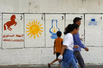 """A Moroccan family walk past electoral paintings representing a political party logos for the upcoming municipal elections in Casablanca, Morocco, Tuesday, Sept. 7, 2021. Party logos are, from left, Constitutional Union (horse), """"Renaissance and Virtue Party"""" (Sun), """"Justice and Development Party"""" (Lamp), and at right """"Authenticity and Modernity Party"""" (Tractor), at the El Fida district of Casablanca. To help illiterate people vote, only party logos will appear on ballot papers, and the numbers seen in the image are allocated to each party for displaying purposes only during the campaign. Elections are scheduled Wednesday 8. (AP Photo/Abdeljalil Bounhar)"""