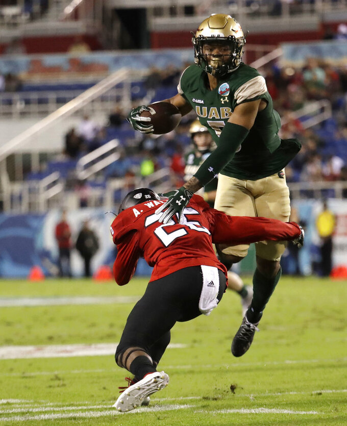 UAB running back Jarrion Street (5) makes a catch as Northern Illinois linebacker Cortez Hogans (25) defends during the first half of the Boca Raton Bowl NCAA college football game, Tuesday, Dec. 18, 2018, in Boca Raton, Fla. (AP Photo/Lynne Sladky)