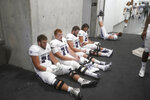 Weber State players wait in the tunnel at Rice-Eccles Stadium during a delay due to inclement weather during the first half of the team's NCAA college football game against Utah on Thursday, Sept. 2, 2021, in Salt Lake City. (AP Photo/Rick Bowmer)