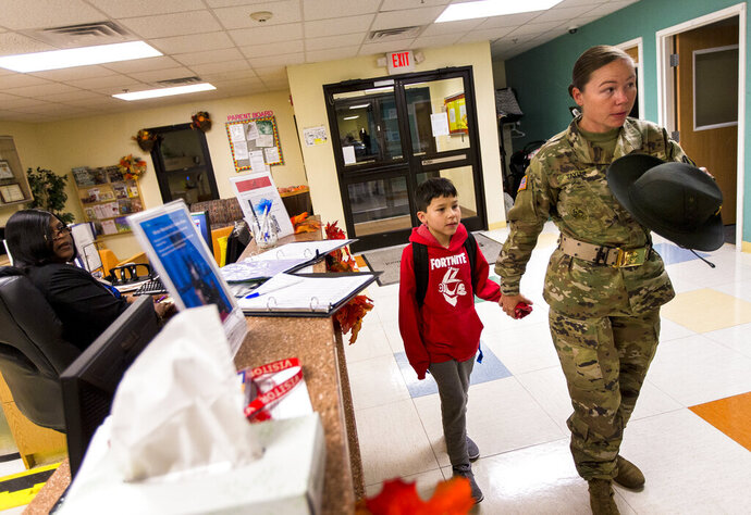 In this Nov. 19, 2019, file photo Dennie Taylor a drill sergeant with the U.S. Army signs in her son Ethan Taylor, 9, at the Imboden Child Development Center at Fort Jackson, S.C. (Andrew J. Whitaker/The Post And Courier via AP)