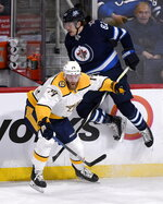 Winnipeg Jets' Mason Appleton (82) is checked by Nashville Predators' Mattias Ekholm (14) during first period NHL hockey action in Winnipeg, Manitoba, Sunday Jan. 12, 2020. (Fred Greenslade/The Canadian Press via AP)