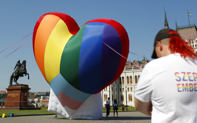 Activists erect a large rainbow-colored heart in front of the country's parliament building in Budapest, Hungary, on Thursday, July 8, 2021. The activists are protesting against the recently passed law they say discriminates and marginalizes LGBT people. (AP Photo/Laszlo Balogh)