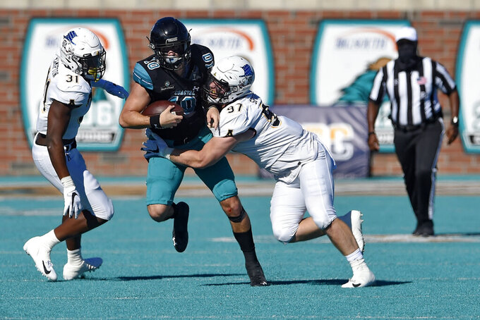Coastal Carolina quarterback Grayson McCall (10) scrambles as Appalachian State's Caleb Spurlin (97) and Nick Hampton close in during the first half of an NCAA college football game Saturday, Nov. 21, 2020, in Conway, S.C. (AP Photo/Richard Shiro)