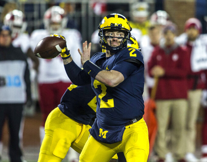 "File-This Nov. 17, 2018, file photo shows Michigan quarterback Shea Patterson (2) throwing a pass in the second quarter of an NCAA college football game against Indiana in Ann Arbor, Mich. The good news for the Wolverines was Patterson's confirmation that he'll be back in 2019. ""I don't know if it was a decision,"" Patterson said. ""I think it was just an announcement."" Patterson, the Mississippi transfer, said he wants to enjoy another season at Michigan.   (AP Photo/Tony Ding, File)"
