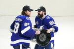 Tampa Bay Lightning right wing Nikita Kucherov (86) hands the Stanley Cup to goaltender Andrei Vasilevskiy after Game 5 of the NHL hockey Stanley Cup finals against the Montreal Canadiens, Wednesday, July 7, 2021, in Tampa, Fla. (AP Photo/Gerry Broome)