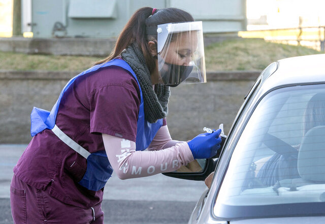 Bobbie Pendleton prepares to give a flu shot in the morning at a drive-thru flu clinic at Bristol Motor Speedway, Thursday, Nov. 19, 2020, in Bristol, Tenn. The Sullivan County Regional Health Department was hosting two drive-thru locations for the