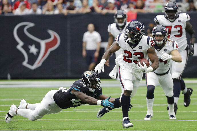 Houston Texans running back Carlos Hyde (23) runs past Jacksonville Jaguars middle linebacker Myles Jack (44) during the first half of an NFL football game Sunday, Sept. 15, 2019, in Houston. (AP Photo/David J. Phillip)