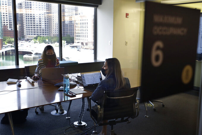 Interior designers Stephanie Jones, left, and Tara Martin, right, work in a conference room at the design firm Bergmeyer, Wednesday, July 29, 2020, at the company's offices, in Boston. To reduce the risk of spreading the coronavirus, the firm implemented one-way routes throughout the office, added higher cubicle walls, requires masks when not at the desk, added hand sanitizer stations and put in lots of signs to make sure rules are clear. (AP Photo/Steven Senne)
