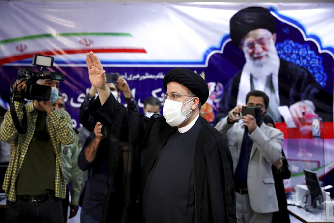 Ebrahim Raisi, head of Iran's judiciary waves to media as he attends at the Interior Ministry to register his candidacy for the June 18 presidential elections at the elections headquarters of the Interior Ministry in Tehran, Iran, Saturday, May 15, 2021. (AP Photo/Ebrahim Noroozi)