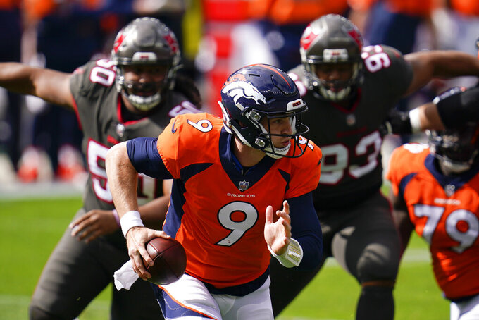 Denver Broncos quarterback Jeff Driskel scrambles under pressure from Tampa Bay Buccaneers nose tackle Vita Vea, left, and defensive end Ndamukong Suh, right, during the first half of an NFL football game Sunday, Sept. 27, 2020, in Denver. (AP Photo/David Zalubowski)