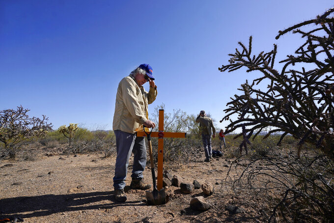 """Alvaro Enciso, part of the Tucson Samaritans volunteer group, pauses as he and a group of other volunteers place a new cross at the site of the migrant who died in the desert some time ago, on Tuesday, May 18, 2021, in the desert near Three Points, Ariz. Enciso says he plants three or four crosses each week. """"Can you imagine what their families go through, not knowing what happened to them?"""" (AP Photo/Ross D. Franklin)"""