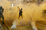 FILE - In this Aug. 3, 2019, file photo, a protester throws back a tear gas canister during a confrontation with police in Hong Kong. Many in Hong Kong took to the streets in 2019 hoping to salvage rights of free speech and association denied to residents of mainland China, where public dissent is treated as subversive and punishable by long prison terms. (AP Photo/Vincent Thian, File)