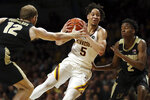 Minnesota's guard Amir Coffey controls the ball through the defense of Purdue's Evan Boudreaux and Eric Hunter Jr. during the first half of an NCAA basketball game Tuesday, March 5, 2019, in Minneapolis. (AP Photo/Stacy Bengs)