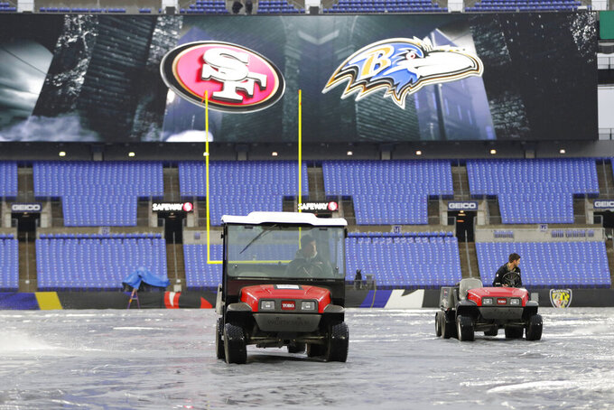 Members of the ground crew use blowers to help dry off the tarp in preparation of an NFL football game between the Baltimore Ravens and the San Francisco 49ers, Sunday, Dec. 1, 2019, in Baltimore, Md. (AP Photo/Julio Cortez)