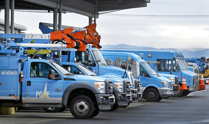 FILE - This Jan. 14, 2019, file photo shows Pacific Gas & Electric vehicles parked at the PG&E Oakland Service Center in Oakland, Calif. A decision was announced Friday, May 1, 2020, that Pacific Gas & Electric Corp. will sweep out three quarters of its board of directors to start with a mostly clean slate when it emerges from a bankruptcy case triggered by deadly wildfires ignited in Northern California by the utility's neglected electrical grid. (AP Photo/Ben Margot, File)