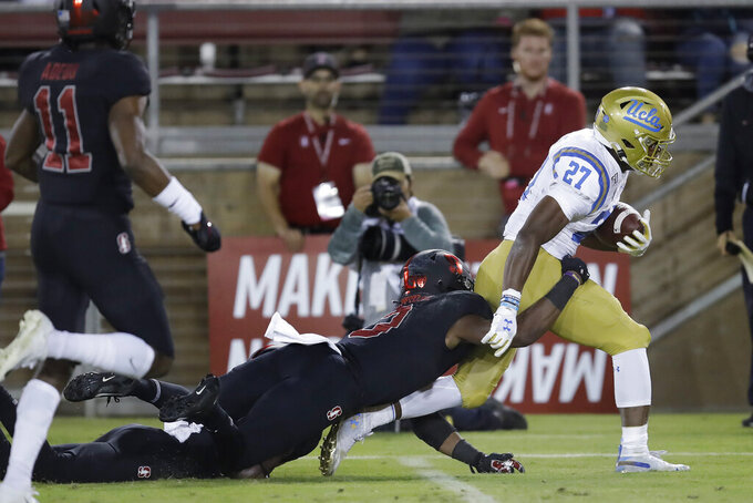UCLA's Joshua Kelley, right, is tackled by Stanford's Malik Antoine during the first half of an NCAA college football game Thursday, Oct. 17, 2019, in Stanford, Calif. (AP Photo/Ben Margot)